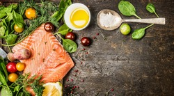 Raw salmon fish fillet with spoon of salt, fresh herbs and spices on rustic wooden background, top view, banner for website with cooking concept.