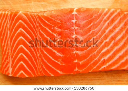 raw salmon fish piece on wooden tray isolated on white background