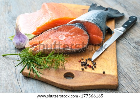 Raw salmon fish steaks with fresh herbs on cutting board