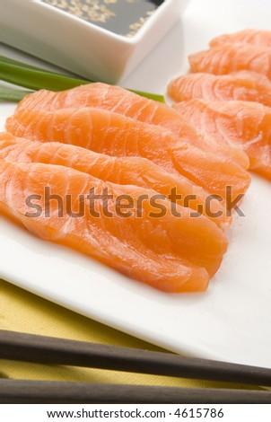 raw salmon over white dish with soy sauce