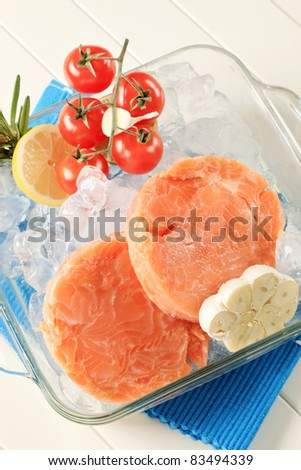Raw salmon patties and other ingredients on ice - stock photo