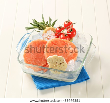 Raw salmon patties and other ingredients on ice