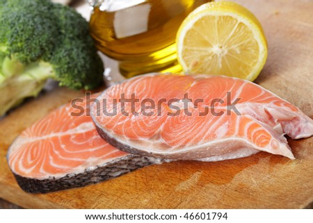 Raw salmon steaks, broccoli, lemon, and olive oil on a wooden cutting board