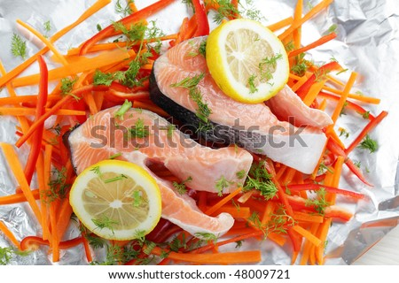 Raw salmon steaks with lemon and vegetables on a foil