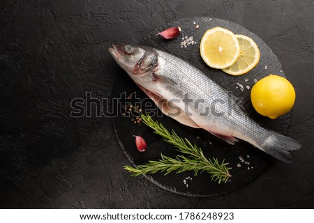 Raw sea bass with fresh rosemary and lemon on stone plate on black concrete background.Top vie,copy space. Photo stock ©
