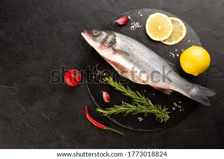 Raw sea bass with fresh rosemary,lemon,cherry pepper,garlic and tomato on stone plate on black concrete background.Top vie,copy space. Photo stock ©