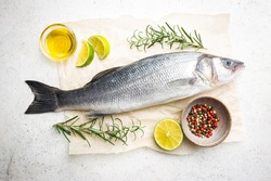 Raw seabass fish with rosemary and spices on white background, top view
