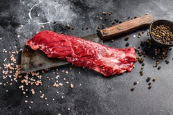 Raw skirt, machete steak on a meat cleaver. Black background. Top view