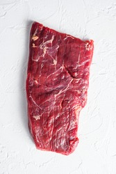 Raw skirt or flank steak,on a white stone background top view vertical