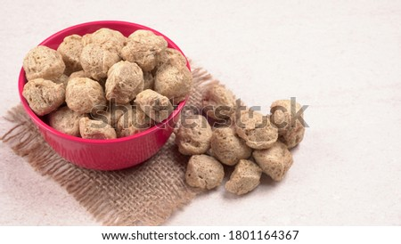Raw soya chunks in bowl on dark background. Healthy, nutritious soybean meat, chunks in a white bowl. Vegan food concept.