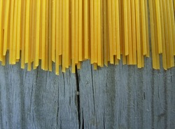 raw spaghetti on the background of old wood. background for a site with food