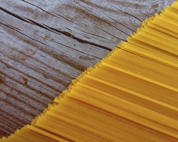 raw spaghetti on the background of old wood. diagonale background for a site with food