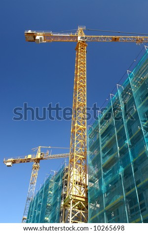 Raw state residential highrise and two yellow jib cranes over clear blue sky