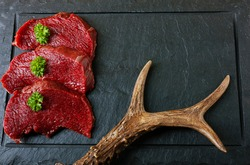 Raw steak meat from roe deer on the bridlic  chopping board. Roe deer antler as a decoration. Copy space for text.