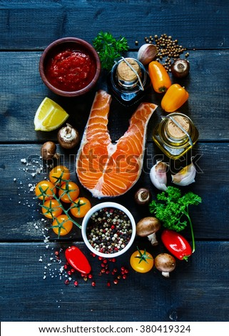 Raw steak of salmon with fresh ingredients for tasty cooking on rustic wooden background, top view, banner. Healthy food concept.