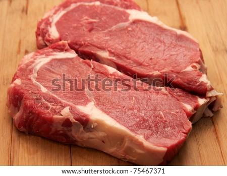 Raw Steak - raw rib eye steaks on the cutting board