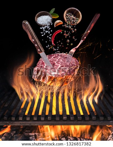 Raw Steak ribeye cooking. Conceptual picture. Steak with spices and cutlery under burning grill grate.