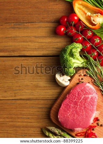 Raw Steak with green asparagus and vegetables on wooden board - stock photo