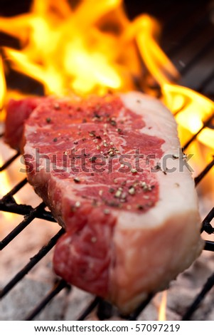 Raw steak with pepper on the barbecue