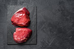 raw steaks fillet Mignon prepared for cooking. Beef tenderloin. Black background. Top view. Space for text