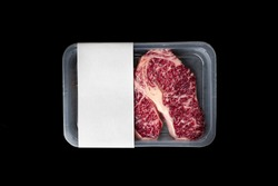 Raw Striploin marbled beef steak vacuum Packed isolated on black, logo mockup