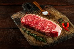 Raw striploin steak (New York) of beef on a board with seasonings, salt and red pepper