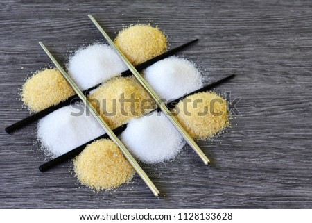 Raw sugar  and granulation sugar inside the chopsticks chessboard with grey wooden background