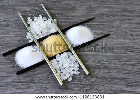 Raw sugar , crystalline sugar and granulation sugar insidw the chopsticks chessboard with grey wooden background