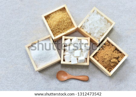 Raw sugar, rock sugar, granulation sugar, and cube sugar in the wooden box with wooden spoon beside