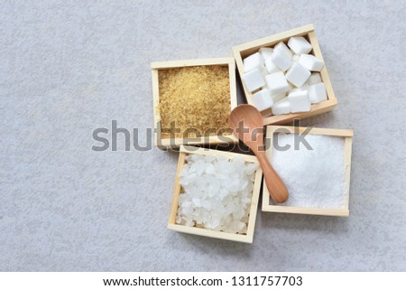 Raw sugar, rock sugar, granulation sugar, and cube sugar in the wooden box with wooden spoon on top