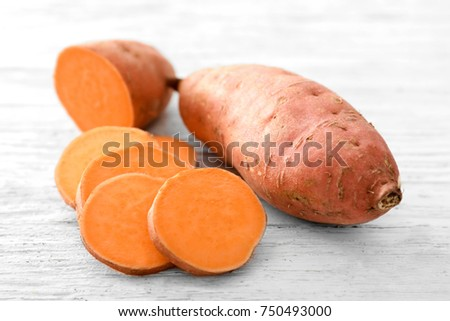 Raw sweet potato on wooden table #750493000