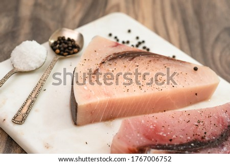 Raw swordfish. Two pieces of fresh raw fish steaks with salt and black pepper close up on marble cutting board on wooden kitchen table Foto stock ©