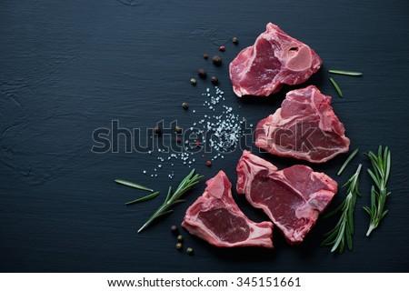 Raw T-bone lamb steaks with seasonings on a black wooden surface
