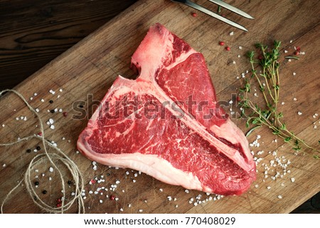 raw t bone steak of beef on the butcher's Board with pepper, salt, herbs, close twine, top view