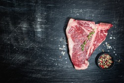 Raw T-bone Steak with fresh herbs and oil on black background, top view