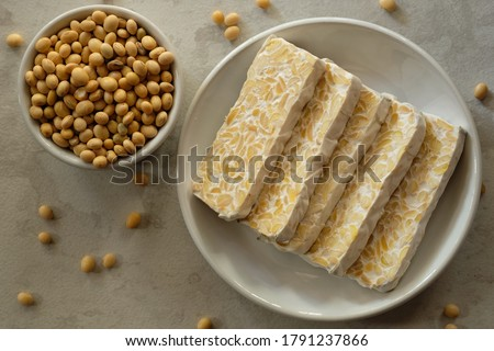 Raw tempeh or tempe. tempeh slices in white ceramic bowls and on a marble table. raw soybean seeds in a white ceramic bowl. Tempe is a traditional Indonesian food made from fermented soybeans.