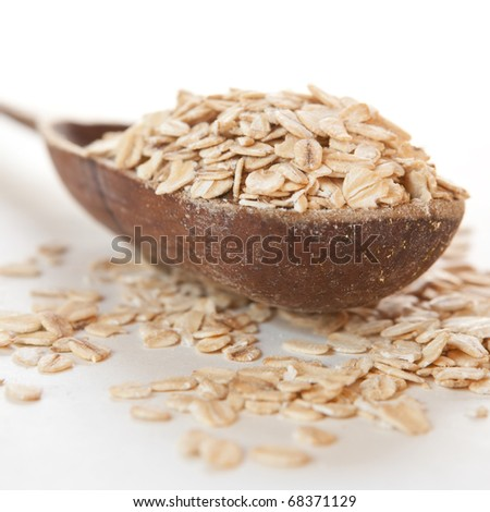 Raw thick rolled oats in a wooden spoon