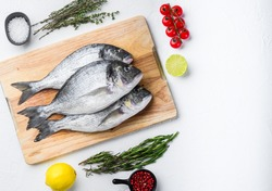 Raw three sea bream or Gilt head bream dorada fish with herbs pepper lime tomato for cooking and grill on white background, top view