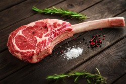 raw Tomahawk steak on wooden background with spices for grilling