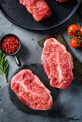 Raw top blade oyster Steak on stone and meat butcher cleaver, marbled beef with herbs tomatoes peppercorns over grey stone surface background top view vertical.