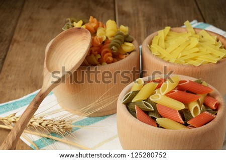 Raw tricolor pasta set on the wooden table