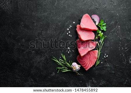 Raw tuna fillet. Seafood on a black stone background. Top view. Free copy space.