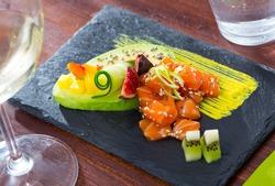Raw tuna tartare served on slate board with ripe avocado and spicy mango sauce ..