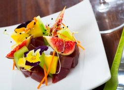 Raw tuna tartare served with cucumbers and figs on white plate