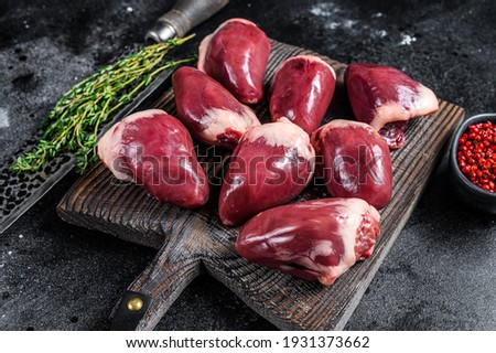 Raw turkey hearts offal with herbs and spices. Black background. Top view. Foto stock ©