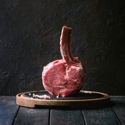Raw uncooked black angus beef tomahawk steak on bone served with salt and pepper on round wooden slate cutting board over dark wooden plank table. Rustic style. Square image