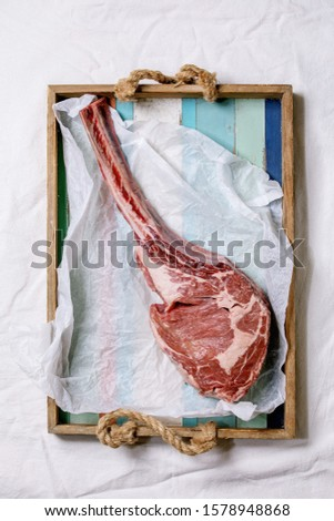 Raw uncooked black angus beef tomahawk steak on bones served on wooden tray with baking paper over white cloth as background. Top view, space.