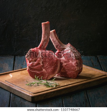 Raw uncooked black angus beef tomahawk steaks on bones served with rosemary, salt and pepper on wooden cutting board over dark wooden plank table. Rustic style. Close up. Square image