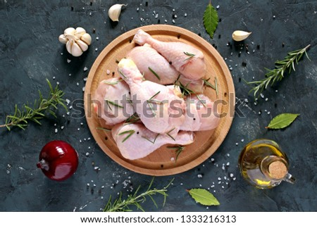 Raw uncooked chicken legs with ingredients for cooking, drumsticks on wooden board. Top view with copy space.