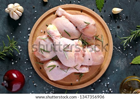 Raw uncooked chickenlegs with ingredients for cooking, drumsticks on wooden board. Top view with copy space.